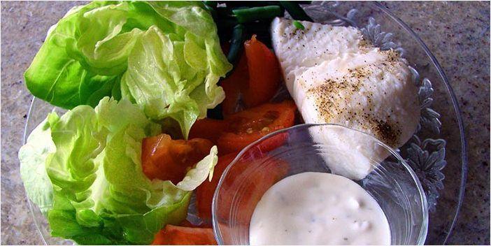 Куриная грудка, овощной салат и соус на тарелке