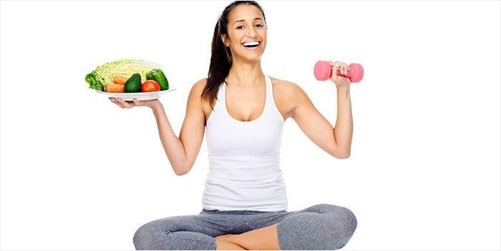 Девушка с тарелкой овощей и гантелью в руках
